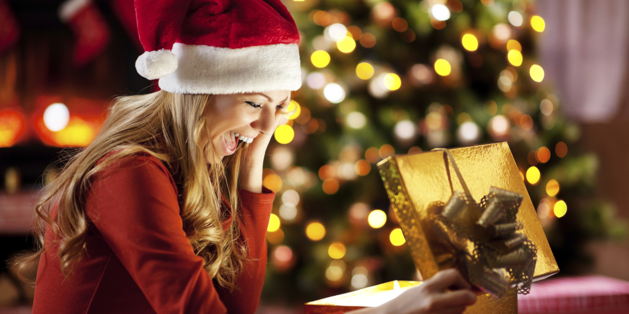 Ecstatic woman opening Christmas presents.